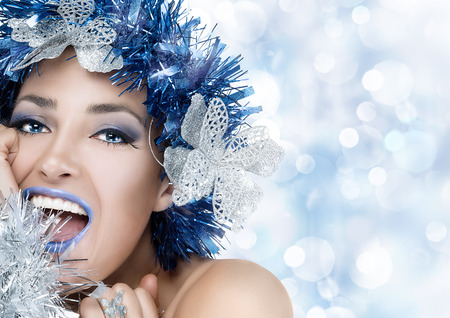 Party girl. Beautiful Christmas woman. Professional holiday makeup and fancy hairstyle. Fashion woman portrait with copy space for text. Vogue style model photo