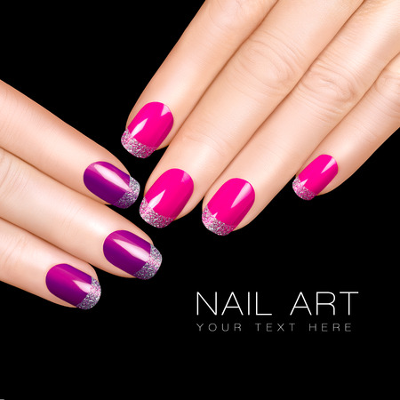 Holiday Nail Art. Luxury nail polish. Glitter nail stickers in purple, pink and silver. Manicure and makeup concept. Closeup hands isolated on black with sample text photo