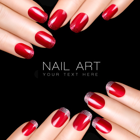 varnish: Holiday Nail Art. Luxury nail polish with glitter French manicure. Manicure and makeup concept. Closeup hands isolated on black with sample text