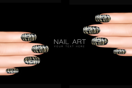 nail varnish: Trend nail polish stickers with animal print. Professional manicure and nail tattoo. Beauty concept. Closeup of manicured fingers isolated on black with sample text Stock Photo
