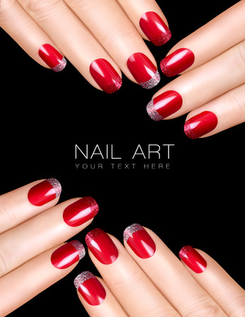 Holiday Nail Art. Luxury nail polish with glitter French manicure in silver and red. Manicure and makeup concept. Closeup hands isolated on black with sample text photo