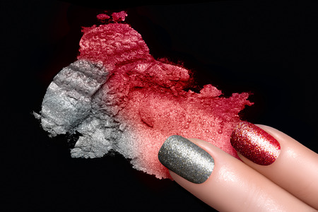 Fingers with trend glitter nails in red and silver. Crushed eye shadow with drops of water. Manicure and makeup concept. Closeup image isolated on black