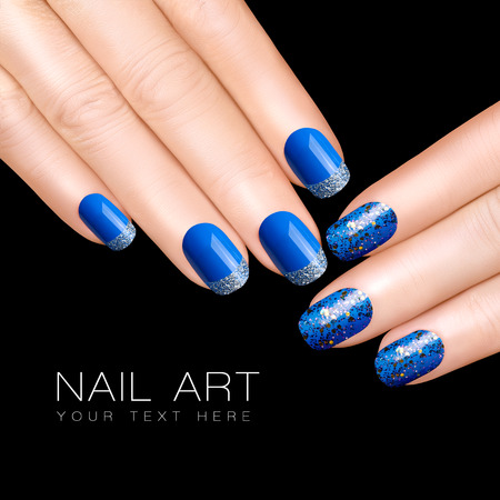 Holiday Nail Art. Luxury blue nail polish. Glitter nail stickers in silver. Manicure and makeup concept. Closeup hands isolated on black with sample text photo