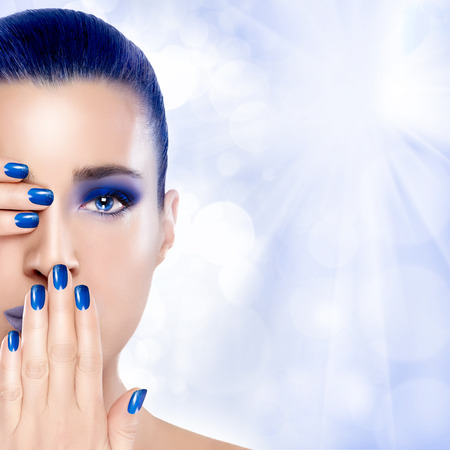 Trendy Blue Makeup. Beautiful young woman with hands on her face covering one eye and mouth. Perfect skin. Nail art and makeup concept. High Fashion Portrait.