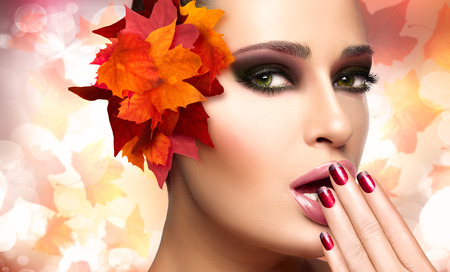 Autumn makeup and nail art trend. Fall beauty fashion girl. Professional makeup and manicure. Closeup portrait on autumnal background with falling leaves