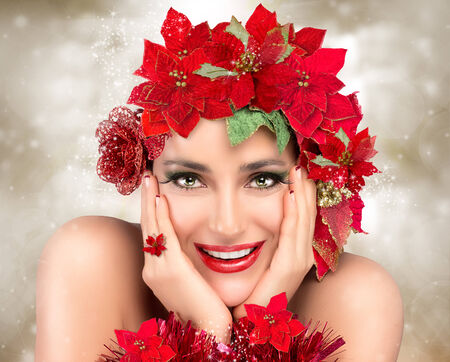 Cheerful christmas girl. Festive makeup, manicure and floral hairstyle in red and green. Beauty fashion christmas. Happy people photo