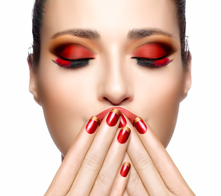 Trendy Red Makeup. Beautiful young woman with hands on her face covering mouth. Perfect skin. Festive Nail art and makeup concept. High Fashion Portrait.