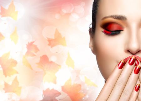 Trucco di autunno e di tendenza nail art. Autunno bellezza fashion girl. Trucco professionale e manicure. Closeup ritratto di metà volto su sfondo autunnale con foglie che cadono