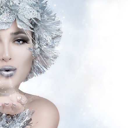 sparkles: Beauty festive fashion. Christmas girl sending a kiss. Magic winter woman with silver stylism. Vogue style model blowing her hand. Sending good wishes. Half face portrait with copy space for text