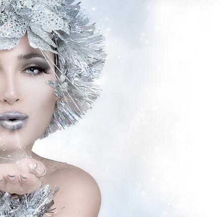 Bellezza della moda di festa. Natale ragazza trasmette un bacio. Donna inverno magico con stilismo d'argento. Modello stile Vogue che soffia la sua mano. Invio di auguri. Mezza volto ritratto con copia spazio per il testo