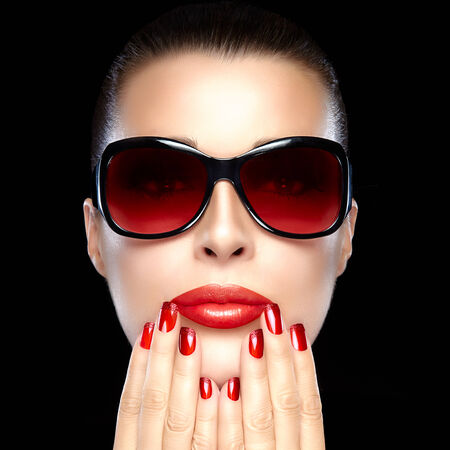 Beautiful fashion model girl with stylish oversized sunglasses. Bright makeup and manicure. High fashion portrait isolated on black background. Beauty and fashion concept. photo