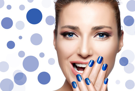nail lacquer: Happy people. Beautiful young woman laughing with hands on face covering half mouth. Perfect skin. Professional manicure and makeup. High Fashion Portrait. Nail Art and Makeup Concept Stock Photo