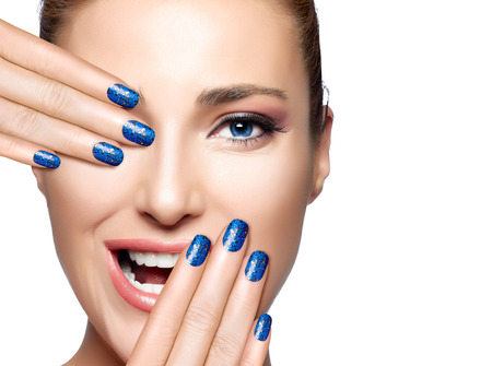 nail lacquer: Happy people. Beautiful young woman laughing with hand on face covering half mouth and one eye. Perfect skin. Professional manicure and makeup. High Fashion Portrait isolated on white with copy space for text. Stock Photo