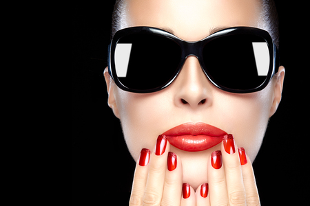 Beautiful fashion model girl with stylish oversized black sunglasses. Bright makeup and manicure. High fashion portrait isolated on black background with copy space for text. Beauty fashion and nail art concept. photo
