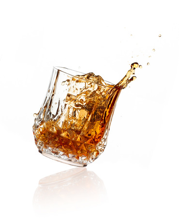 Splashing whisky on glass of cut glass over white background photo
