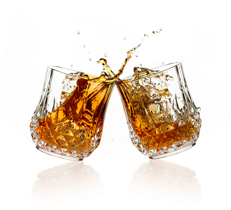 shot: Cheers. A Toast with whiskey. Two glasses clicking together over white background. Splashing whisky on glasses of cut glass