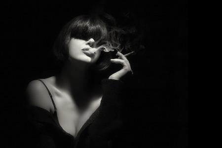 Elegante sensuale giovane donna con frangia alla moda di fumare una sigaretta. Taglio di capelli corto. Alta moda ritratto in bianco e nero con copia spazio per il testo.
