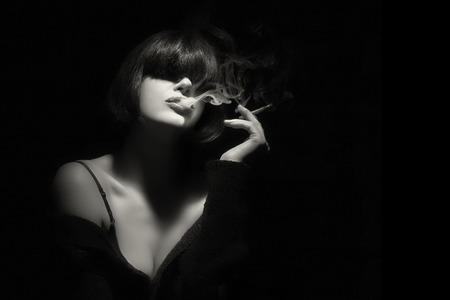 smoking: Stylish sensual young woman with trendy fringe smoking a cigarette. Short hairstyle. High fashion portrait in black and white with copy space for text. Stock Photo