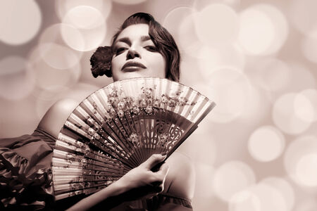 Gypsy Flamenco Festival. Beautiful Andalusian woman with carnation in hair and stylish fan. Spanish beauty. Fine Art portrait in sepia with copy space for text. photo