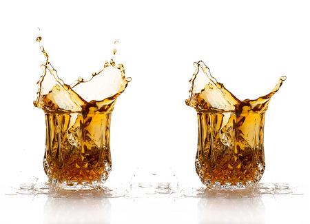 Two Whiskey splash on elegant glass of cut glass isolated on white background photo