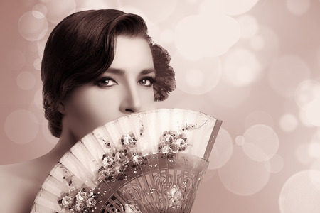 Gypsy girl. Beautiful Andalusian woman with carnation in hair and covering half face with a stylish fan. Spanish beauty. Fine Art portrait in sepia with copy space for text. photo