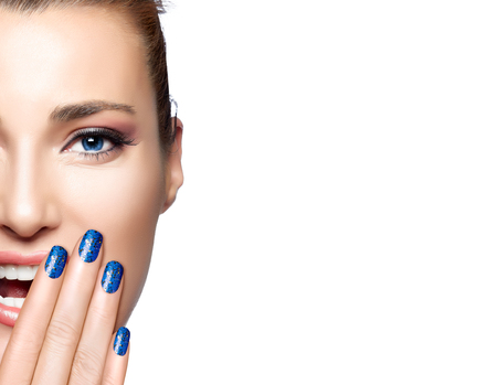 Happy people. Beautiful young woman laughing with hand on face covering half mouth. Perfect skin. Professional manicure and makeup. High Fashion Portrait of half face with copy space for text. Zdjęcie Seryjne