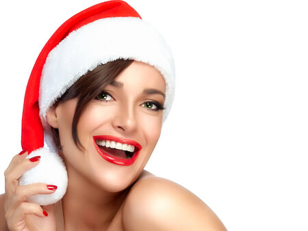 christmas manicure: Happy Christmas girl in Santa hat with a beautiful big smile. Sensual red lips and manicure. Fashion portrait isolated on white background with copy space for text Stock Photo