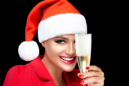christmas manicure: Joyful Christmas girl in Santa hat with a beautiful big smile and champagne glass. Sensual red lips and manicure. Happy people. Fashion portrait isolated on black background