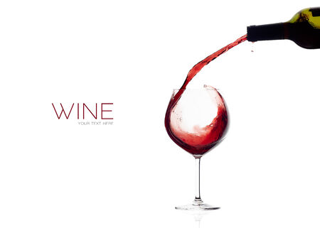 Red wine being poured into balloon glass. Splash. isolated on white with sample text Stock Photo
