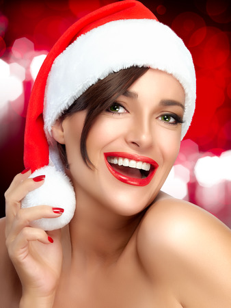christmas manicure: Merry Christmas. Happy Christmas girl in Santa hat with a beautiful big smile. Red lips and manicure Stock Photo