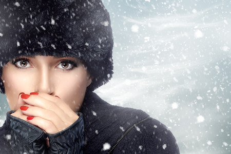 Winter beauty fashion. Lovely girl with trendy fur hat and mittens heating her hands in a snowstorm. Fashion portrait on the winter background. Snowy Day Stock Photo