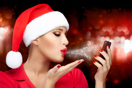 Merry Christmas. Beautiful Christmas girl in Santa hat makes a selfie sending kisses with a smartphone. photo