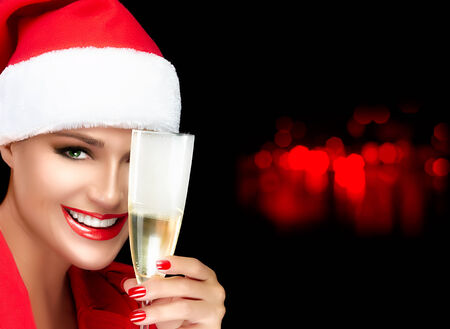 christmas manicure: Joyful Christmas girl in Santa hat with a beautiful big smile toasting with a glass of champagne. Red lips and manicure. Happy people. Christmas greetings concept Stock Photo