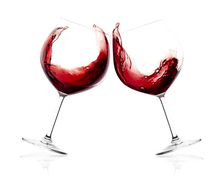 Cheers. A Toast with Red Wine. Splash. Two glasses clicking together over white background. Splashing red wine on lloon glasses Standard-Bild