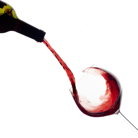 Red wine being poured into balloon glass isolated on white. Splash. Stock Photo