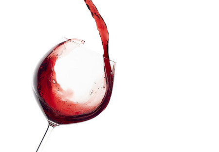 Red wine being poured into balloon glass isolated on white with copy space for text. Splash.