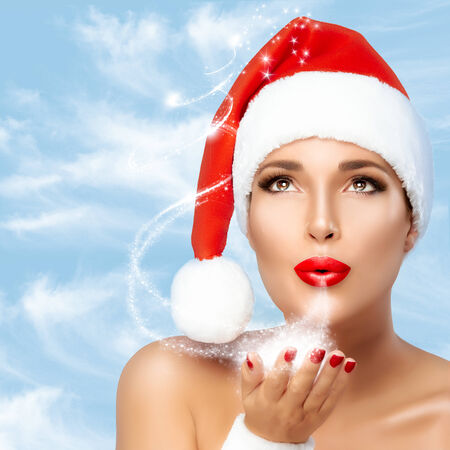 christmas manicure: Magical Christmas girl in Santa hat blowing star dust. Red lips and manicure. Beauty fashion portrait