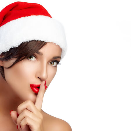 christmas manicure: Beautiful Christmas girl in Santa hat doing a hush sign. Red lips and manicure. Closeup portrait isolated on white with copy space for text
