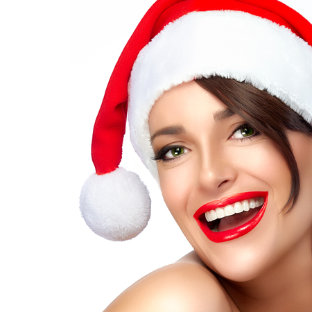 christmas manicure: Happy Christmas girl in Santa hat with a beautiful big smile. Sensual red lips and manicure. Fashion portrait isolated on white