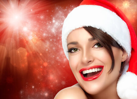 christmas manicure: Merry Christmas. Happy Christmas girl in Santa hat with a beautiful big smile. Sensual red lips and manicure. Fashion portrait with flashing lights