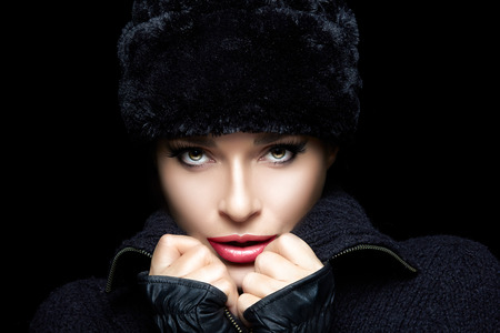 wintry: Winter Beauty. Fashion beautiful girl with trendy fur hat and mittens looking at camera. High fashion portrait. Wintry style