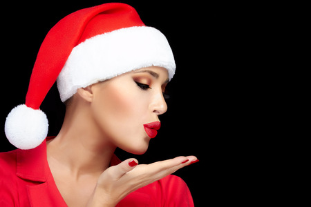 christmas manicure: Merry Christmas. Beautiful Christmas woman in Santa hat sending a kiss. Red lips and manicure. Happy people. Fashion portrait isolated on black with copy space for text.