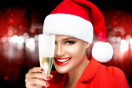 christmas manicure: Joyful Christmas girl in Santa hat with a beautiful big smile and champagne glass. Red lips and manicure. Happy people. Christmas greetings. Fashion portrait over of red and white sparkling lights