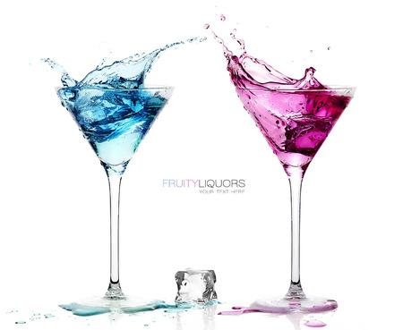 Martini Glazen met Splashing Gekleurde Cocktails met Ice Cube op de tafel. Geïsoleerd op witte backgroun