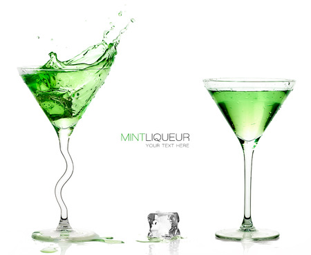 martini splash: Conceptual Elegant Martini Glasses full of Green Cocktails with one one splashing out and Ice Cube on the Table. Isolated on White Background with Copy Space at the Center. Template design with sample text Stock Photo