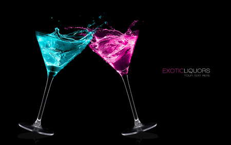 Cocktail glasses with long stems full of colorful liquors making a toast splashing out, close-up isolated on black