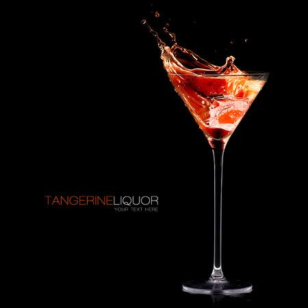Cocktail glass with high stem filled with orange liqueur splashing out on a black background Foto de archivo