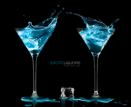 black background: Ice cube between two cocktail glasses filled with blue alcoholic exotic liqueur splashing out, with copy space on black