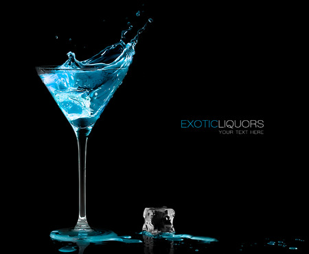 Stemmed cocktail glass with blue alcoholic drink splashing out, close-up isolated on black Foto de archivo