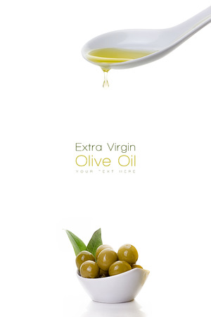 olive: Healthy virgin olive oil dripping from a white ceramic spoon on a sample text with olive seeds on white bowl at the bottom left isolated on white Stock Photo